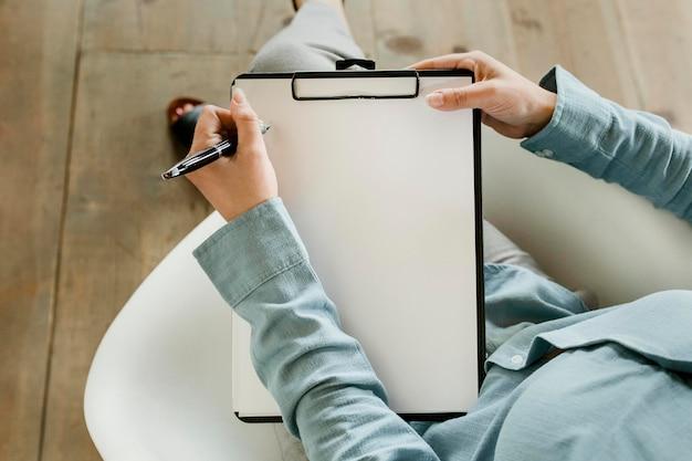 Médico preenchendo registros de saúde em uma maquete de papel