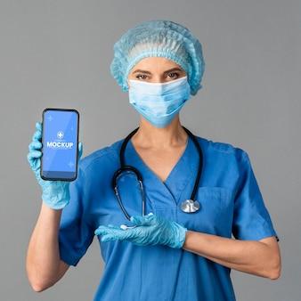 Médico segurando smartphone com tiro médio