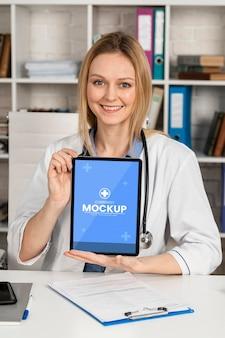Médico sorridente de tiro médio com tablet