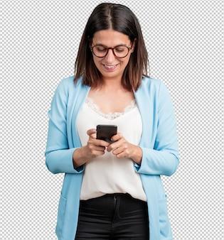 Meio envelhecida mulher feliz e descontraída, tocando o celular