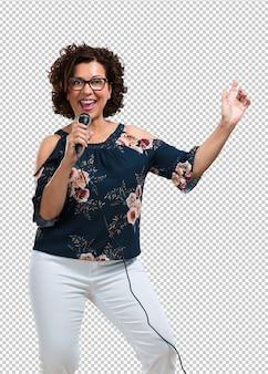 Meio envelhecida mulher feliz e motivada, cantando uma música com um microfone, apresentando um evento ou ter uma festa, aproveite o momento