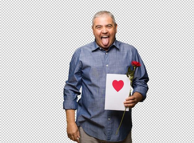 Meio envelhecido homem comemorando dia dos namorados funnny e amigável mostrando a língua