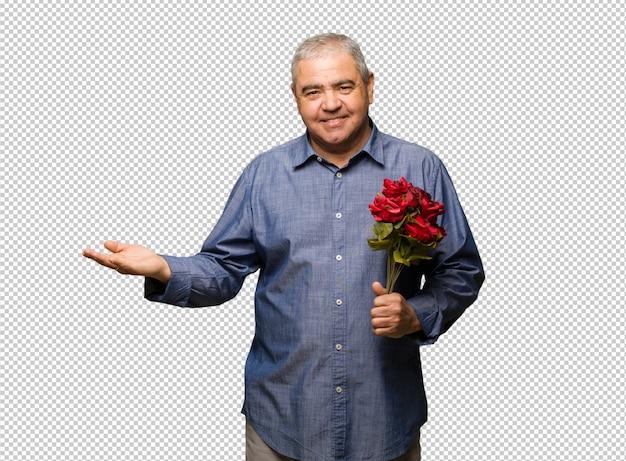 Meio envelhecido homem comemorando o dia dos namorados segurando algo com a mão