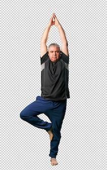 Meio envelhecido homem fazendo exercícios de ioga de corpo inteiro