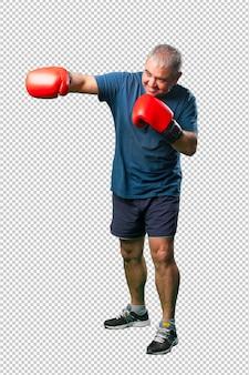Meio envelhecido homem socar com luvas de boxe, corpo inteiro