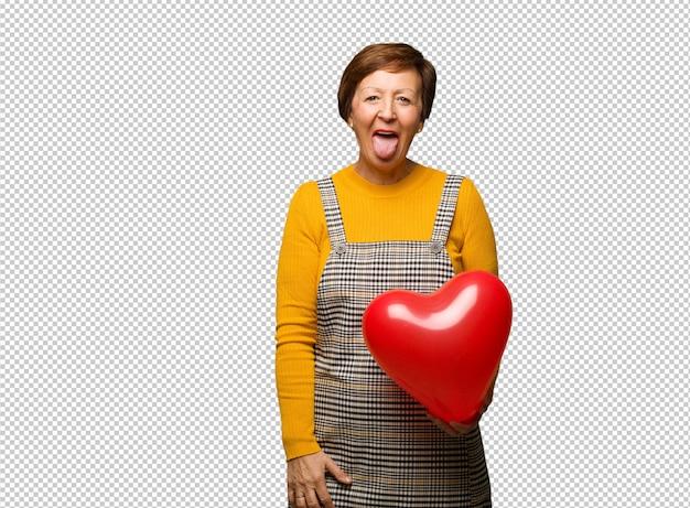 Meio envelhecido mulher comemorando dia dos namorados funnny e amigável mostrando a língua