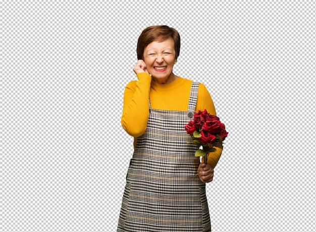 Meio envelhecido mulher comemorando o dia dos namorados, cobrindo as orelhas com as mãos