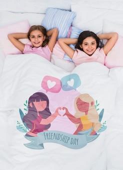 Melhores amigas de relaxamento na cama com giro cobertor mock-up