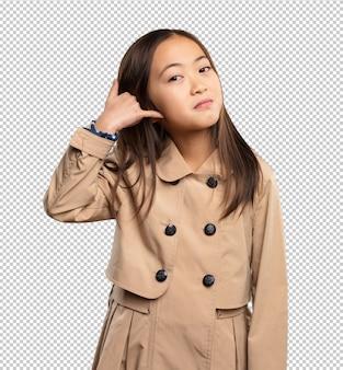 Menina chinesa fazendo gesto de telefone