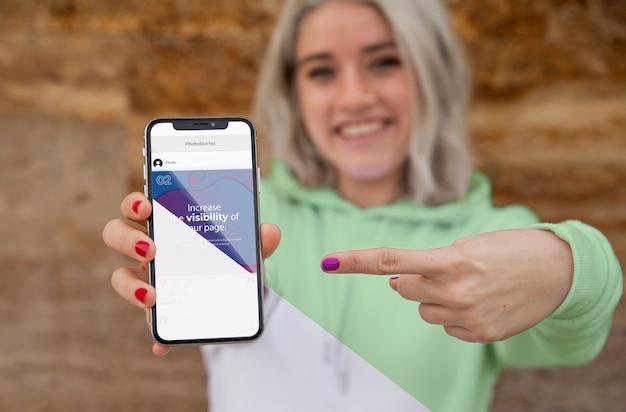 Menina com capuz apontando para celular