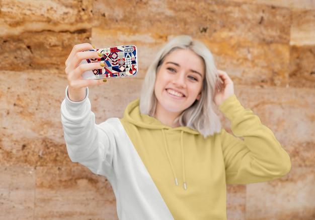 Menina com capuz tomando selfie
