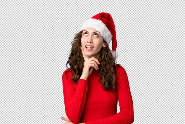 Menina com chapéu de natal, pensando em uma idéia