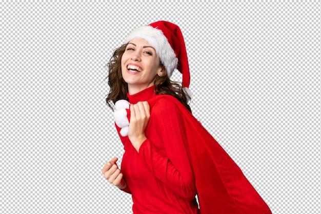 Menina com chapéu de natal segurando uma sacola cheia de presentes