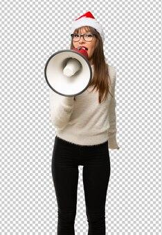Menina com comemorando as férias de natal gritando através de um megafone para anunciar algo