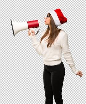 Menina com comemorando as férias de natal gritando através de um megafone para anunciar alguns
