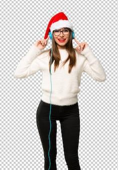 Menina com comemorando as férias de natal ouvindo música com fones de ouvido