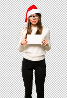 Menina com comemorando as férias de natal, segurando um cartaz branco vazio para inserir um conceito