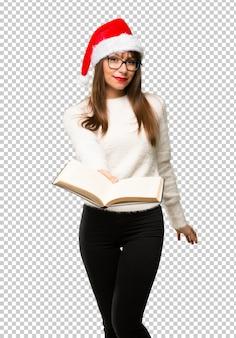 Menina com comemorando as férias de natal segurando um livro e dando a alguém