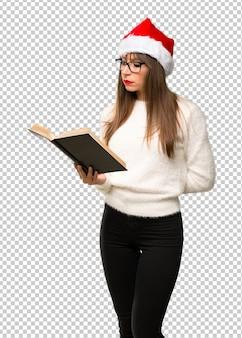 Menina com comemorando as férias de natal segurando um livro e desfrutando de leitura