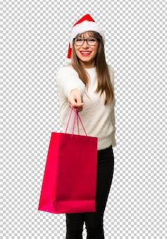 Menina com comemorando os feriados de natal surpreso, mantendo um monte de sacos de compras