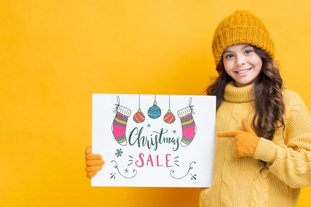 Menina com folha de papel para vendas de natal