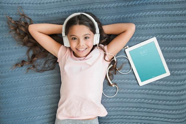 Menina com fones de ouvido ao lado de maquete do tablet