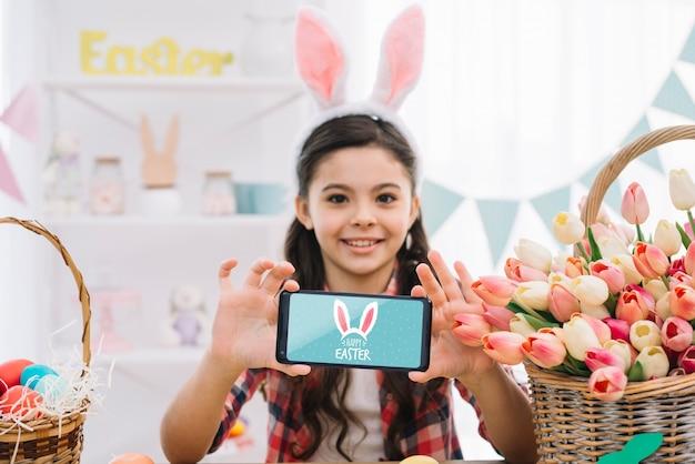 Menina com maquete de smartphone no dia da páscoa