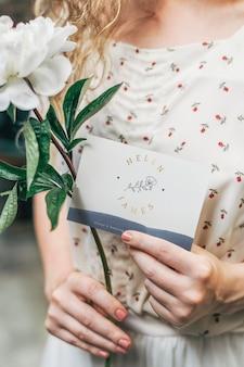 Menina com uma flor de snowboard de paeonia branca e um cartão de maquete