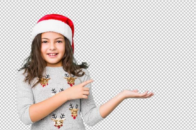 Menina comemorando o dia de natal animado segurando um espaço de cópia na palma da mão.