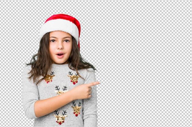 Menina comemorando o dia de natal, apontando para o lado