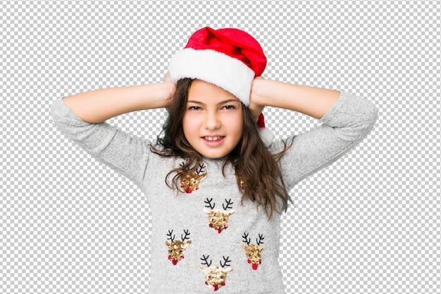Menina comemorando o dia de natal, cobrindo os ouvidos com as mãos, tentando não ouvir som muito alto.