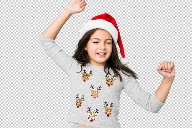 Menina comemorando o dia de natal, comemorando um dia especial, saltos e levante os braços com energia.