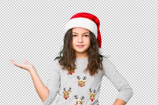 Menina comemorando o dia de natal, mostrando um espaço de cópia em uma palma e segurando a outra mão na cintura.
