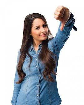 Menina confusa que mostra o polegar para baixo