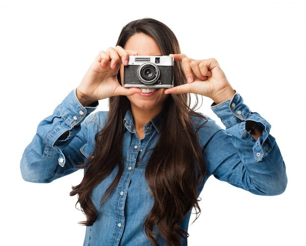 Menina de sorriso com a câmera do vintage