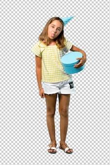Menina em uma festa de aniversário, segurando um presente mostrando a língua para a câmera, olhando engraçado