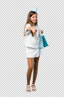Menina em uma festa de aniversário, segurando um saco de presente aponta o dedo para você