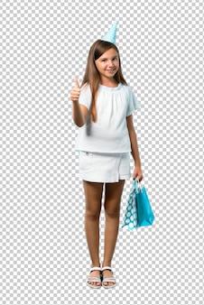 Menina em uma festa de aniversário, segurando uma sacolinha dando um polegar para cima gesto e sorrindo