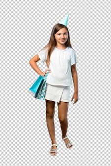 Menina em uma festa de aniversário, segurando uma sacolinha posando com os braços no quadril