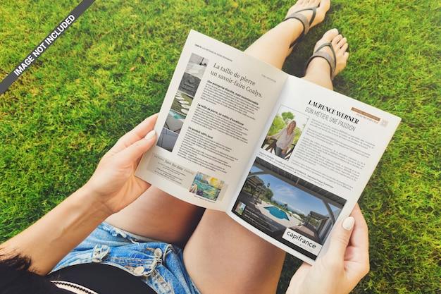 Menina lê uma revista sobre a maquete de grama