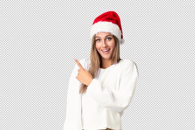 Menina loira com chapéu de natal, apontando o dedo para o lado