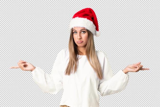 Menina loira com chapéu de natal apontando para as laterais tendo dúvidas
