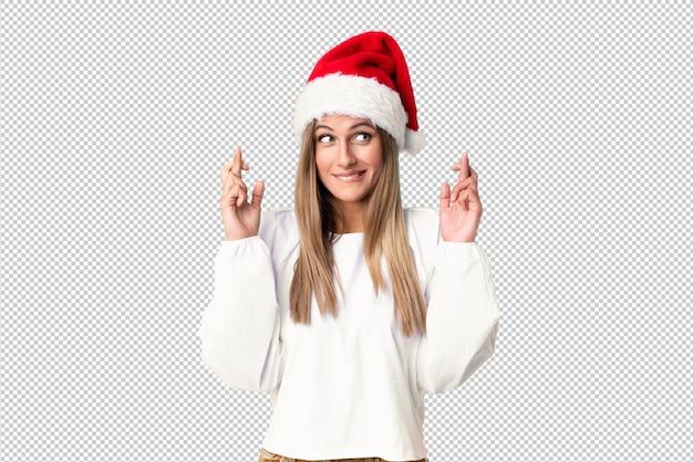 Menina loira com chapéu de natal com dedos cruzando