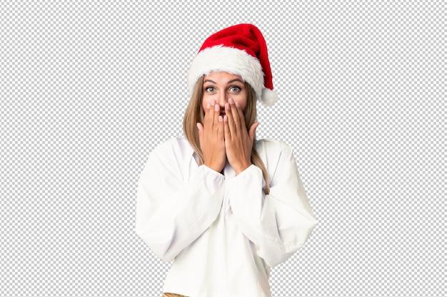 Menina loira com chapéu de natal com expressão facial de surpresa