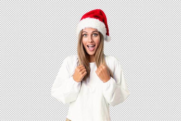 Menina loira com chapéu de natal comemorando uma vitória