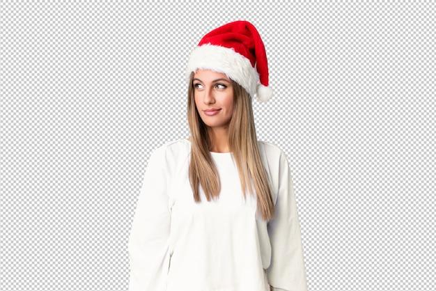 Menina loira com chapéu de natal em pé e olhando para o lado