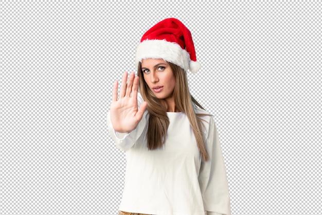 Menina loira com chapéu de natal, fazendo o gesto de parada com a mão