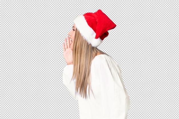 Menina loira com chapéu de natal gritando com a boca aberta