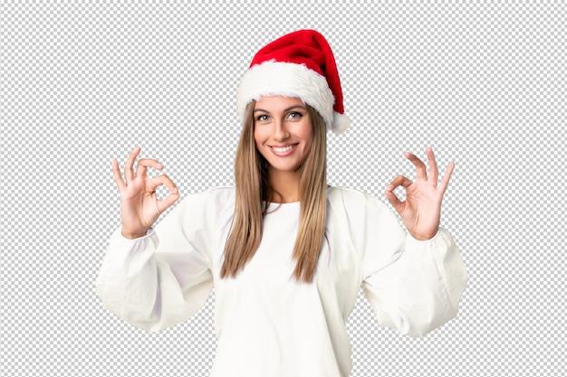 Menina loira com chapéu de natal, mostrando um sinal de ok com os dedos