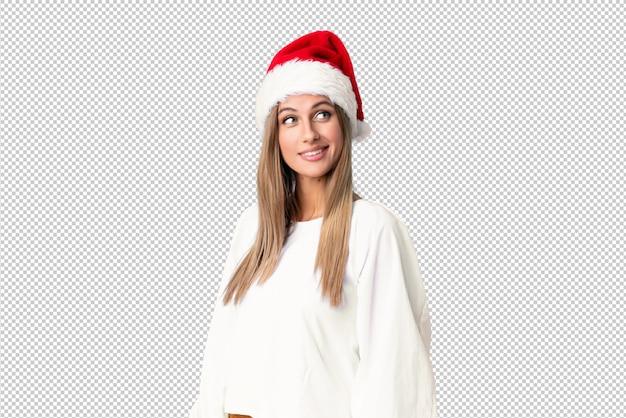 Menina loira com chapéu de natal rindo e olhando para cima